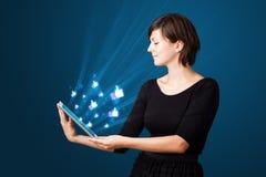 Jovem mulher que olha a tabuleta moderna com luzes abstratas e assim Fotos de Stock