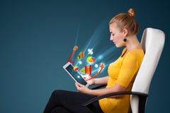 Jovem mulher que olha a tabuleta moderna com luzes e va abstratos Foto de Stock Royalty Free