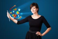 Jovem mulher que olha a tabuleta moderna com luzes e va abstratos Foto de Stock