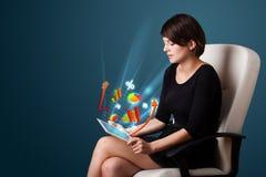 Jovem mulher que olha a tabuleta moderna com luzes e va abstratos Imagens de Stock Royalty Free