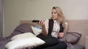 Jovem mulher que olha a tevê e os canais do interruptor na cama Imagem de Stock
