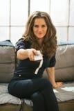 Jovem mulher que olha a tevê no apartamento do sótão Fotografia de Stock Royalty Free