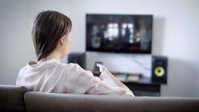 Jovem mulher que olha a tevê sentar-se no sofá na sala de visitas, comuta os canais usando o controlo a distância vídeos de arquivo