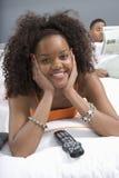 Jovem mulher que olha a tevê no quarto Fotos de Stock