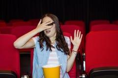 Jovem mulher que olha um filme 3d assustador Foto de Stock