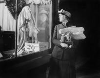 Jovem mulher que olha uma exposição da janela ao alcançar em sua bolsa (todas as pessoas descritas não são umas vivas mais longo  imagens de stock royalty free