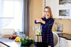 Jovem mulher que põe frutas e legumes no misturador eletrical fotografia de stock