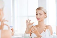 Jovem mulher que põe sobre lentes de contato no banheiro foto de stock