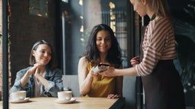 Jovem mulher que paga pelo almoço no café usando o smartphone que fala à empregada de mesa