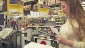 Jovem mulher que paga pelo cartão plástico da compra na verificação geral no vídeo da metragem do estoque do supermercado vídeos de arquivo