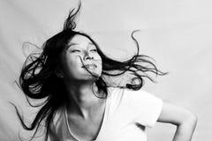 Jovem mulher que passa rapidamente o cabelo Fotografia de Stock Royalty Free