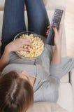 Jovem mulher que passa um fim de semana de relaxamento em casa que olha a tevê Fotografia de Stock Royalty Free