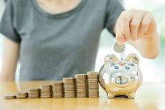 Jovem mulher que põe uma moeda em um dinheiro-caixa-fim u Fotografia de Stock Royalty Free