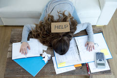 Jovem mulher que pede o esforço do sofrimento da ajuda que faz contas domésticas do documento da contabilidade