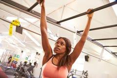 Jovem mulher que pendura das barras de macaco em um gym fotos de stock