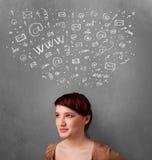 Jovem mulher que pensa com ícones sociais da rede acima de sua cabeça Fotos de Stock