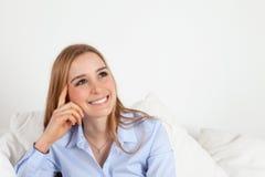 Jovem mulher que pensa em um sofá foto de stock royalty free