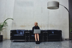 Jovem mulher que pensa sobre ideias novas para o trabalho na rede ao guardar sobre seu laptop dos joelhos foto de stock royalty free