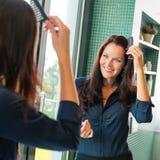 Jovem mulher que penteia o banheiro do espelho do pente do cabelo Imagens de Stock