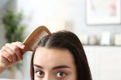 Jovem mulher que penteia o cabelo em casa imagem de stock royalty free
