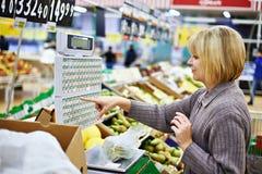 Jovem mulher que pesa peras na loja Imagens de Stock
