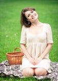 Jovem mulher que picnicing no parque Imagem de Stock