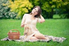 Jovem mulher que picnicing no parque Imagem de Stock Royalty Free