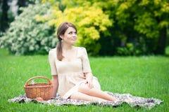 Jovem mulher que picnicing no parque Fotografia de Stock
