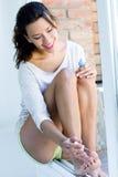 Jovem mulher que pinta seus pregos em casa Foto de Stock Royalty Free
