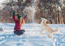 Jovem mulher que plaing com o golden retriever na caminhada do inverno Foto de Stock