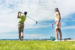 Jovem mulher que pratica o movimento correto durante a classe do golfe foto de stock
