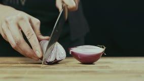 Jovem mulher que prepara cebolas em uma mesa de cozinha video estoque