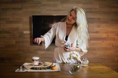 Jovem mulher que prepara o café da manhã na tabela no apartamento moderno imagem de stock