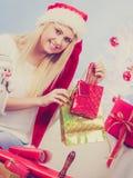 Jovem mulher que prepara presentes para o Natal imagem de stock