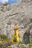 Jovem mulher que prepara-se para ir na rota de escalada da corda fotografia de stock
