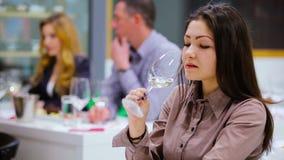 Jovem mulher que prova um vinho branco no degustation video estoque