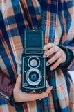 Jovem mulher que realiza na câmera velha do vintage das mãos Fotógrafo da menina fotos de stock royalty free