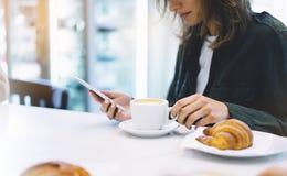 A jovem mulher que realiza na fêmea entrega o telefone celular e a bebida café do aroma ou chá quente no tempo de café da manhã,  imagem de stock