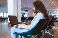 Jovem mulher que realiza um port?til no teclado de datilografia do rega?o dentro no aeroporto fotos de stock