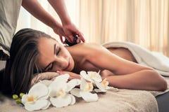 Jovem mulher que recebe a massagem de pedra quente no centavo dos termas e do bem-estar imagens de stock