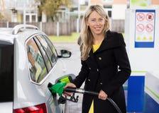 Jovem mulher que reenche o carro no posto de gasolina fotografia de stock