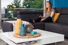 Jovem mulher que refrigera e que olha a tevê do sofá fotografia de stock royalty free