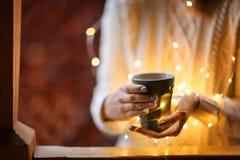 Jovem mulher que relaxa ao beber o chá fotografia de stock