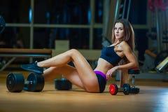 Jovem mulher que relaxa após ter feito flexões de braço, mulher que exercita na esteira da aptidão com pesos no gym imagens de stock royalty free