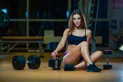 Jovem mulher que relaxa após ter feito flexões de braço, mulher que exercita na esteira da aptidão com pesos no gym fotos de stock royalty free