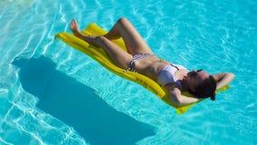 Jovem mulher que relaxa com o colchão de ar na piscina do ar livre filme