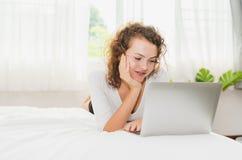 Jovem mulher que relaxa com o portátil na cama na manhã fotografia de stock