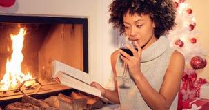 Jovem mulher que relaxa com um livro e um vinho tinto foto de stock royalty free