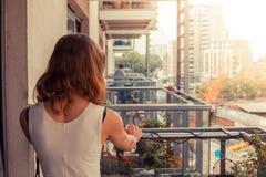 Jovem mulher que relaxa em seu balcão imagens de stock royalty free