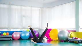 Jovem mulher que relaxa fazendo exercícios de esticão vídeos de arquivo